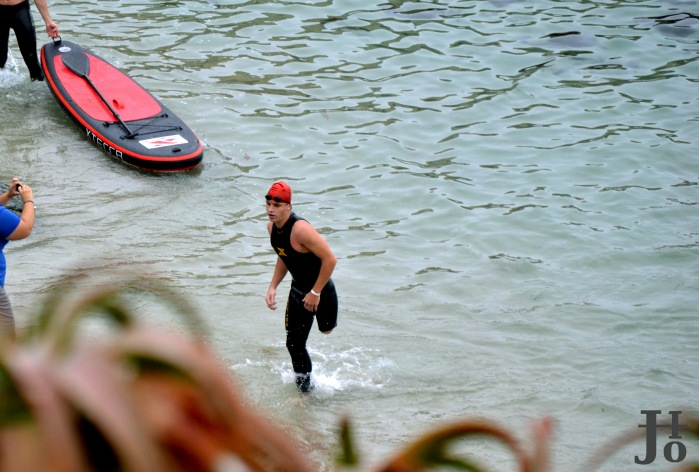 Athlete rushes out of the water after a 1 mile swim through La Jolla Cove.
